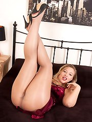 Looking slinky in her velvet dress and sheer shiny pantyhose, Beth gets down to self pleasure on the bed.