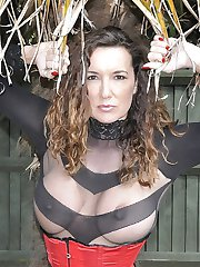 Busty brunette Strapon Jane is outdoors in a red corset and high heels sporting a big black strapon