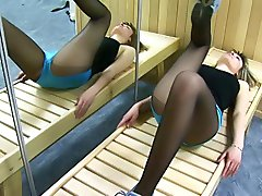 Gymnast in black pantyhose doing workouts