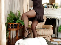 Cutie in glossy stockings putting strap-on in action in hot game with a guy