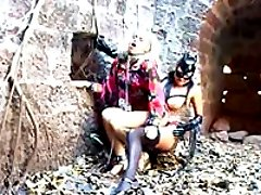 Fetish cat lady in stockings and latex mask disciplines and strapon-fucks blonde lesby outdoors