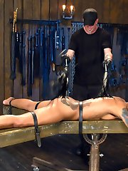 Her head is in a wooden stock, her wrist are restrained with metal cuffs and she is mounted on a spinning platform. She is toyed with flogged, and made to endure breath control at the hands of her sadistic captor. The rewarding orgasm has her eyes rolled back in her head as she spins out of control in ecstasy.Next Skin is confined to a little space and restrained with leather belts. Again her head is locked into a stock and her nipples are tied to her toes. Fear comes over her face as her breath is controlled. She gasps for air when he releases just to fall short as her mouth is covered again. Now Skin is face down, legs spread and made helpless with leather straps. She suffers through a brutal flogging and bastinado with hopes of a final orgasm. Her pussy is stuffed with a massive didlo, and her slutty ass is fingered. Noe that her pussy has given all of it's juices, we fuck Skin's throat until she has swallowed every drop of her whore juices.