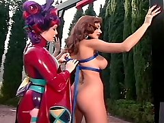 Gorgeous redhead slave getting fettered by a kinky latex geisha
