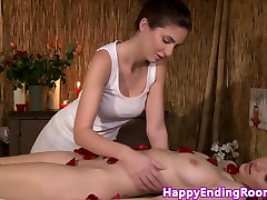 Oiled up lesbian beauties on a massage table