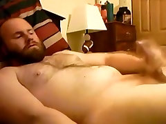 Bearded bear stroking on bed
