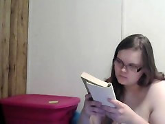 Nerdy pregnant girl reading naked in bed
