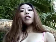 Asian beauty in bikini smoking at pool