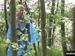 Sara Rose is walking through the woods, wearing a see through plastic raincoat,