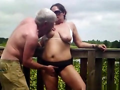 Crazy mature couple has sex on a bridge in nature