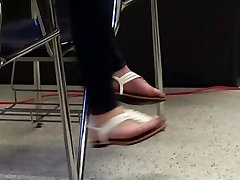 College girl with blue toes dangles her sexy feet from table