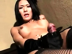 Asian Tranny strokes her cock with gloves